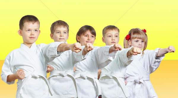 Five little athletes hits a punch arm on a yellow background Stock photo © Andreyfire