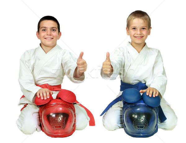 Karate children sit in a ritual pose with helmets and point the finger isolated  Stock photo © Andreyfire
