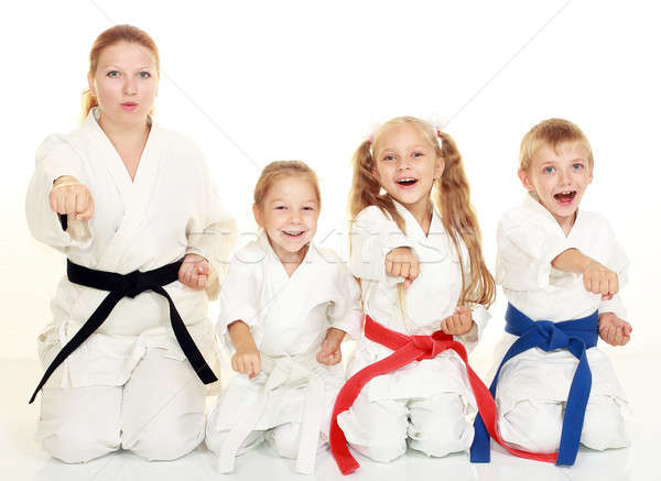 A boy sitting with his sister and mom with her daughter  in a ritual pose karate and beat his fist Stock photo © Andreyfire