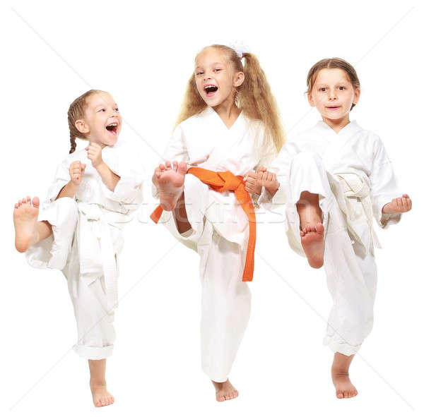 Three cheerful girl on a white background in kimono perform a punch leg Stock photo © Andreyfire