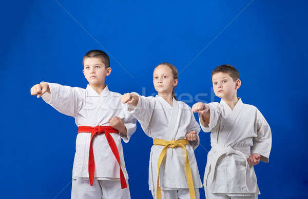 Three young athletes are beating punch hand Stock photo © Andreyfire