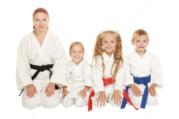 Mother with her daughter and a boy with his sister sitting in a karate pose ritual Stock photo © Andreyfire