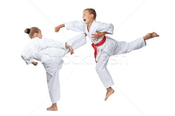 Gyaku-tsuki and mavashi geri are beating sportsmens in karategi Stock photo © Andreyfire