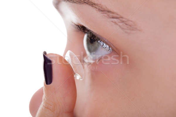 Woman inserting a contact lens Stock photo © AndreyPopov