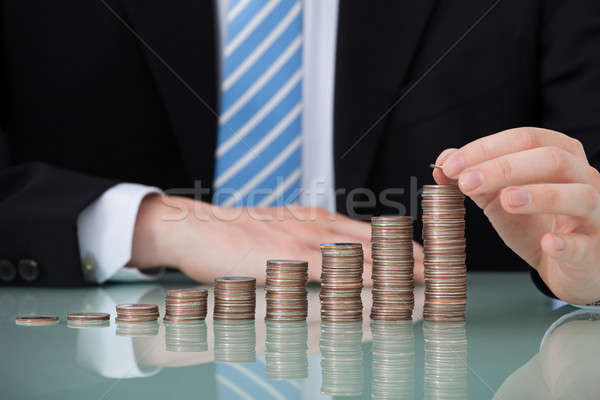 Businessman With Coins Stacked As Bar Graph Stock photo © AndreyPopov