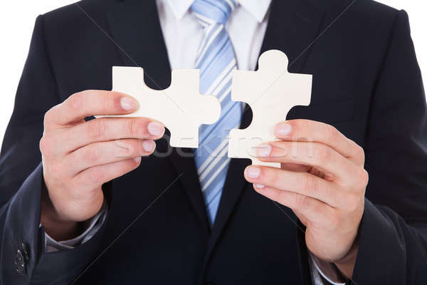 Businessman Solving Jigsaw Puzzle Stock photo © AndreyPopov
