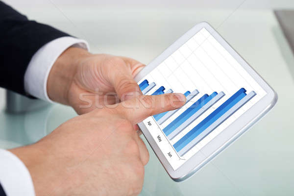 Businessman Comparing Graphs On Digital Tablet At Office Desk Stock photo © AndreyPopov