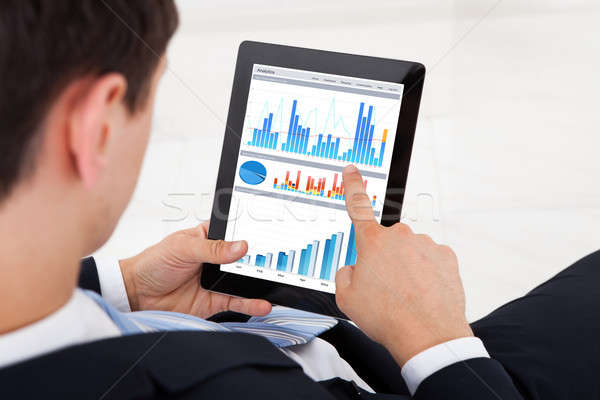 Businessman Comparing Graphs On Digital Tablet In Office Stock photo © AndreyPopov