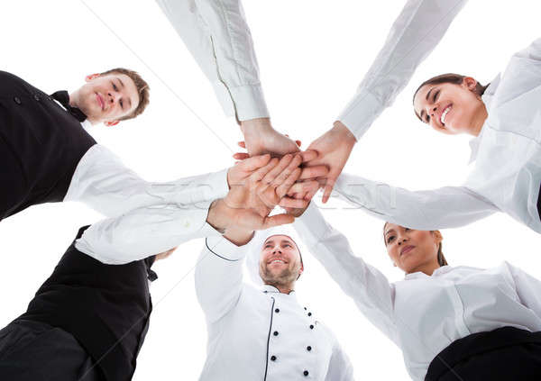 Waiters and waitresses stacking hands Stock photo © AndreyPopov