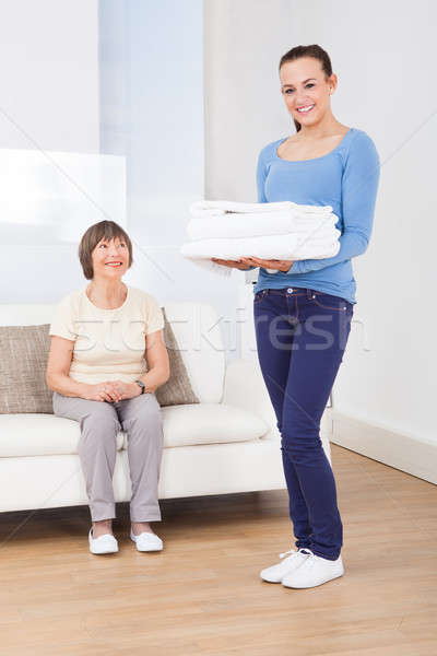 Caretaker Carrying Towels With Senior Woman Sitting On Sofa Stock photo © AndreyPopov