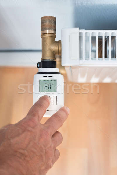 Person's Hand Adjusting Temperature On Thermostat Stock photo © AndreyPopov