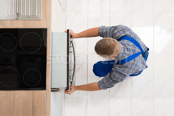 Man Repairing Kitchen Oven Stock photo © AndreyPopov