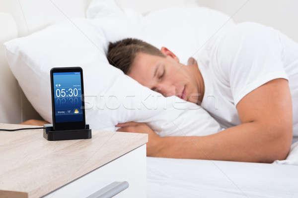 Man Sleeping With Alarm On Mobile Phone Stock photo © AndreyPopov