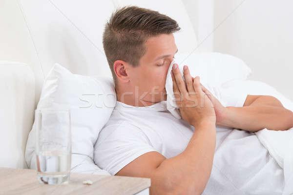 Homem assoar o nariz moço cama lenço papel Foto stock © AndreyPopov