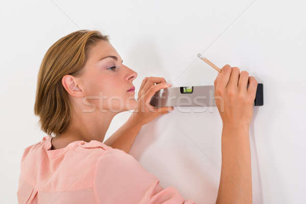 Woman Taking Measurements Of The Wall Stock photo © AndreyPopov