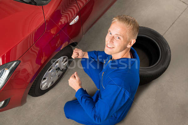 Mechanic Fixing Car Tire With Wrench Stock photo © AndreyPopov