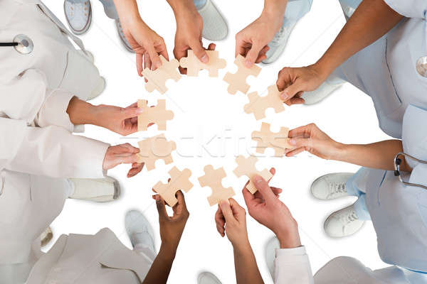 Stock photo: Medical Team Holding Jigsaw Pieces In Huddle