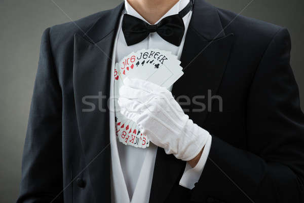 Stock photo: Magician Putting Fanned Out Cards In Suit