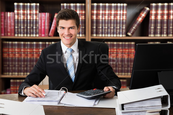 Confident Lawyer Using Calculator At Desk Stock photo © AndreyPopov