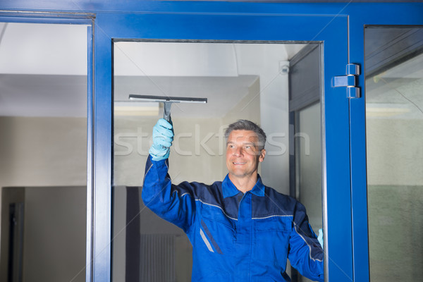 Male Worker Cleaning Glass With Squeegee Stock photo © AndreyPopov