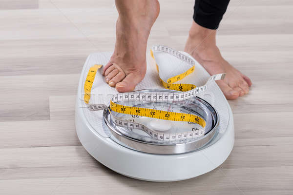 Person Feet Standing On Weighing Scale Stock photo © AndreyPopov