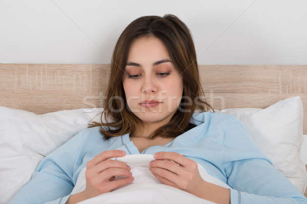 Stock photo: Young Woman Holding Thermometer