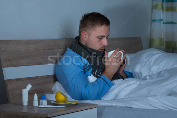Man Sitting On Bed Drinking Cup Of Tea Stock photo © AndreyPopov