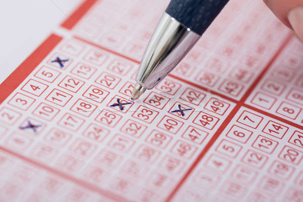 Woman Marking Number On Lottery Ticket With Pen Stock photo © AndreyPopov