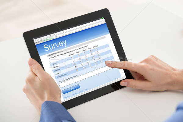 Woman Filling Online Survey Form On Digital Tablet Stock photo © AndreyPopov