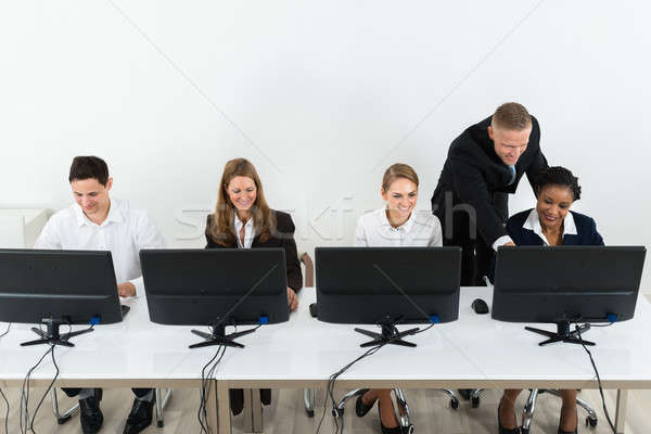 Businessman Helping His Colleagues In The Office Stock photo © AndreyPopov