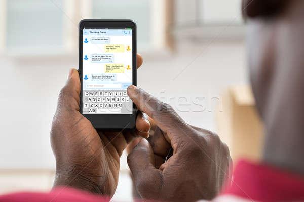 Stock fotó: Afrikai · férfi · küldés · üzenet · közelkép · mobiltelefon