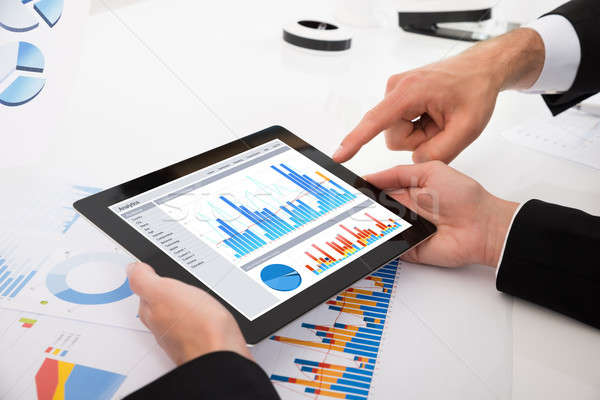 Businesspeople Comparing Graphs On Digital Tablet Stock photo © AndreyPopov