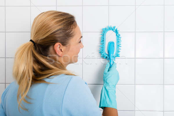 Smiling Woman Cleaning The Tiled Wall Of The Bathroom Stock photo © AndreyPopov