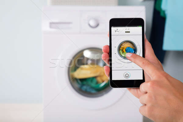 Person Operating Washing Machine Using Cellphone Stock photo © AndreyPopov