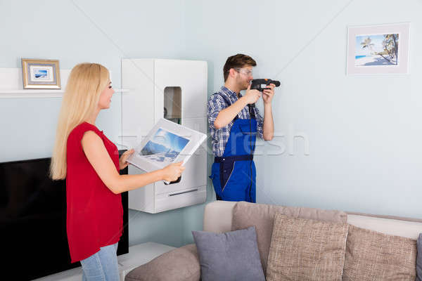 Young Man Using Power Drill On White Wall At Home Stock photo © AndreyPopov