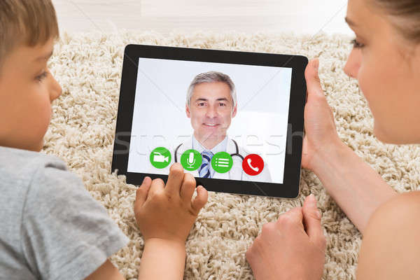 Woman And Son Video Conferencing With Doctor On Rug Stock photo © AndreyPopov