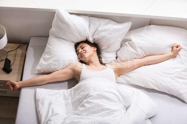 álmos nő nyújtás ágy kilátás fiatal nő Stock fotó © AndreyPopov