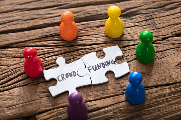 Crowd Funding Jigsaw Pieces Surrounded By Colorful Figurines Stock photo © AndreyPopov
