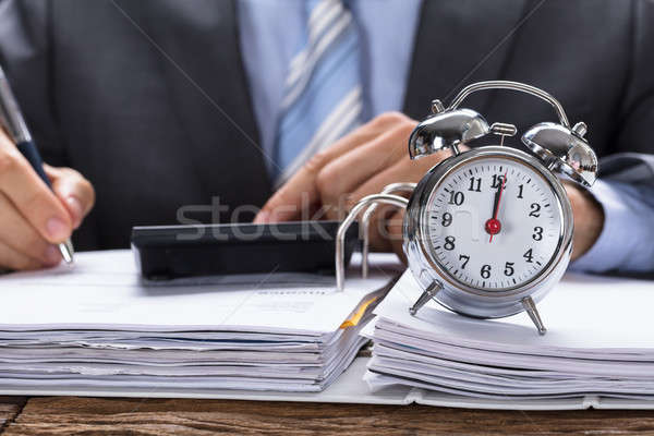 Businessman Calculating Invoice With Alarm Clock On Documents Stock photo © AndreyPopov
