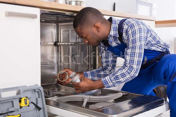 Tamir bulaşık makinesi genç Afrika mutfak Stok fotoğraf © AndreyPopov