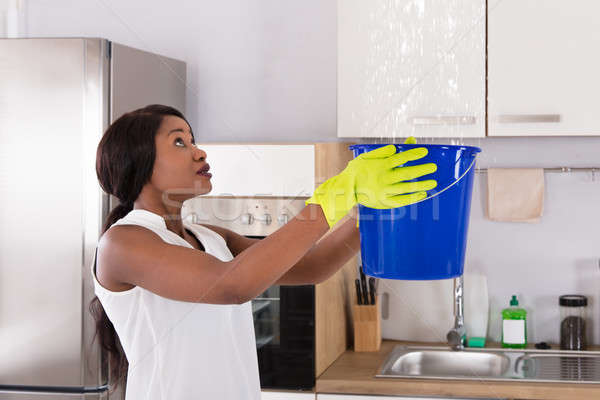 Woman Holding Bucket While Water Droplets Leak From Ceiling Stock photo © AndreyPopov