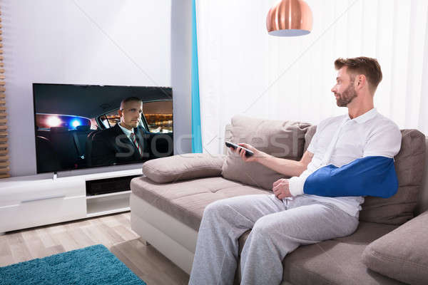 Young Man With Fractured Hand Watching Movie On Television Stock photo © AndreyPopov