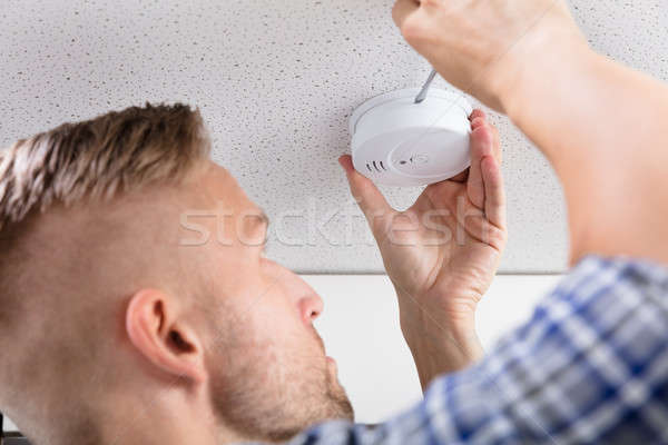 Person's Hand Using Screwdriver To Install Smoke Detector Stock photo © AndreyPopov