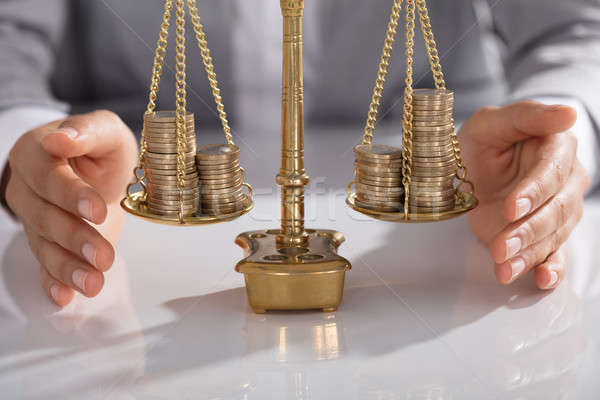 Businessperson Protecting Justice Scale With Stacked Of Coins Stock photo © AndreyPopov