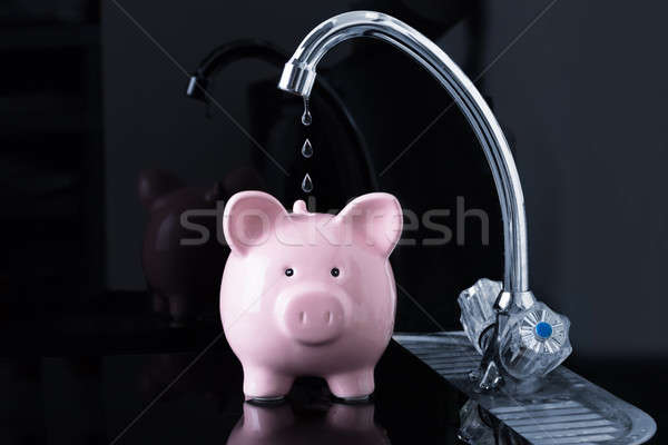 Falling Dripping Water Drop From The Faucet Inside The Piggybank Stock photo © AndreyPopov