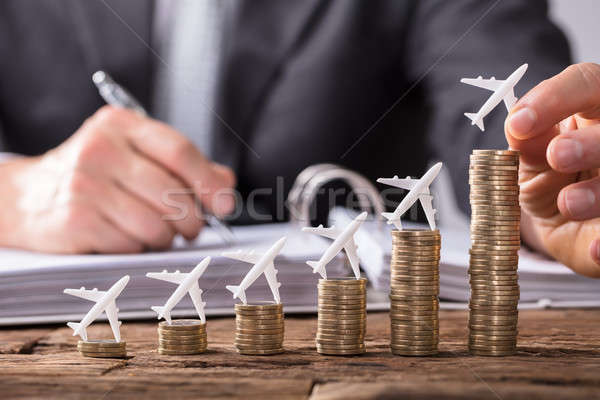 Human Hand Placing Small Aeroplane On Increasing Stacked Coins Stock photo © AndreyPopov