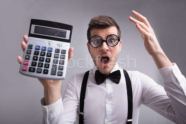 Shocked Young Man Holding Calculator Stock photo © AndreyPopov