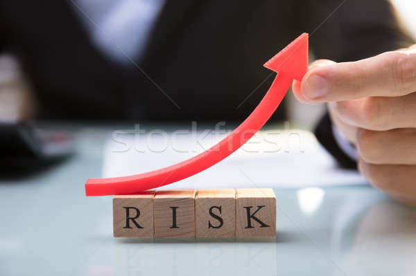 Businessperson Holding Red Arrow Over Risk Blocks Stock photo © AndreyPopov