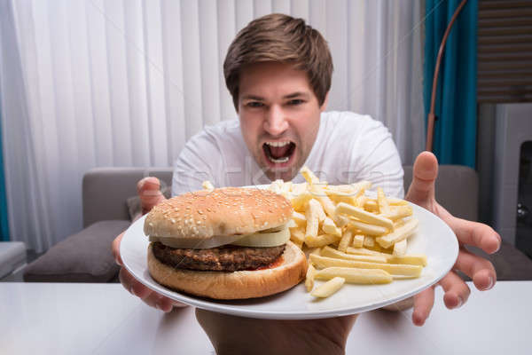 Man Taking Junk Food On Plate Stock photo © AndreyPopov