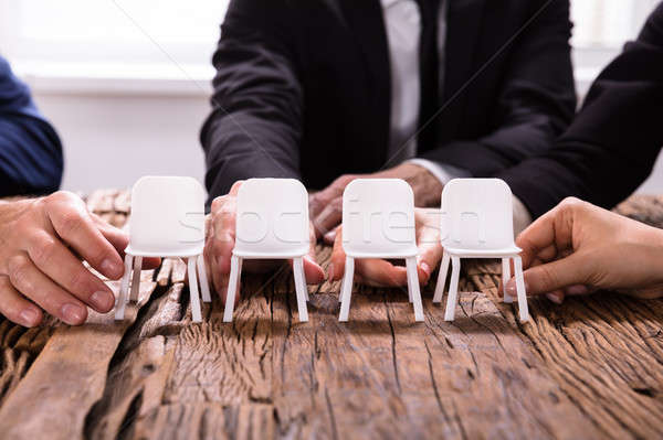 Businesspersons's Hands Arranging Chairs In A Row Stock photo © AndreyPopov
